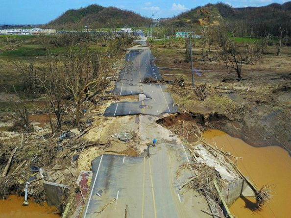 A man rides his bicycle through a damaged road in Toa Alta, west of San Juan, Puerto Rico, on September 24, 2017 following the passage of Hurricane Maria. / AFP PHOTO / Ricardo ARDUENGO (Photo credit should read RICARDO ARDUENGO/AFP/Getty Images)